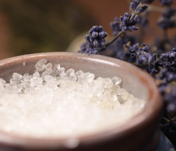 Bath salt in blue ceramic vessel on wooden desk with lavender