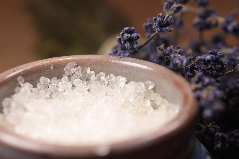 Bath salt in blue ceramic vessel on wooden desk with lavender
