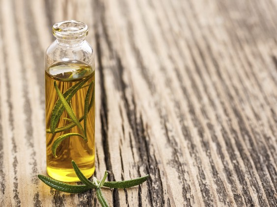 Rosemary oil on rustic wooden background